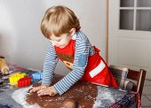 stock photo of ginger bread  - Adorable little boy baking ginger bread cookies for Christmas in home - JPG