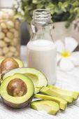 Avocado, macadamia and milk on a white table