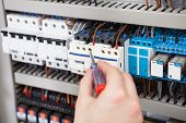 Electrician Examining Fusebox With Screwdriver