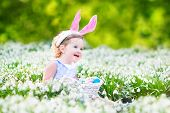 Adorable Toddler Girl Wearing Bunny Ears in a sunny garden with first white spring flowers