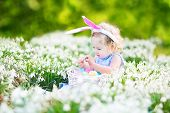 Beautiful toddler girl wearing bunny ears playing with Easter eggs