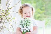 Beautiful Curly Toddler Girl sitting in a white rocking chair next to a big garden view window