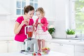 Sweet Laughing Toddler Girl And Her Beautiful Young Mother Making Fresh Strawberry And Other Fruit