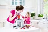Happy Toddler Girl And Her Beautiful Young Mother Making Fresh Strawberry And Other Fruit