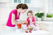 Little Laughing Toddler Girl And Her Beautiful Young Mother Making Fresh Strawberry And Other Fruit