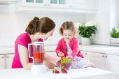 Beautiful Laughing Toddler Girl And Her Young Mother Making Fresh Strawberry And Other Fruit