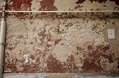 Deteriorating Red Plaster With Pipes And Cables