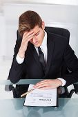 Tired Businessman With Invoice At Desk