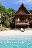 Mature Man Watching The Ocean From A Tropical Bungalow