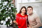 Young Couple Sitting By Cristmas Tree