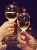 picture of spare  - Romantic young couple toasting wineglasses in front of lit fireplace - JPG