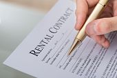 stock photo of rental agreement  - Cropped image of hand filling rental contract form on desk - JPG