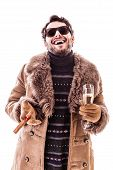 foto of hustler  - a young man wearing a sheepskin coat isolated over a white background holding a cigar and a glass with champagne - JPG