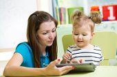 Mother And Kid Are Looking To Play And Read Tablet Computer