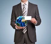 Businessman in suit hold empty card and Earth