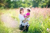 Beautiful Woman Playing With A Toddler Girl In A Sunny Summer Field