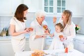 Four Generations Of Women Having Fun Together Baking An Apple Pie In A Beautiful White Kitchen