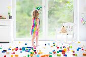 Cute Laughing Toddler Girl Playing With Colorful Blocks, Building An Airplane In A Sunny Bedroom