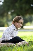 Five year old boy sitting on blanket in park