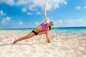 image of legs apart  - Woman with one arm up and legs apart in yoga position on sandy beach with beautiful ocean background