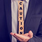 Businessman Holding The Word - Caution