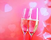 Champagne Flutes With Golden Bubbles On Blur Decorative Hearts Background