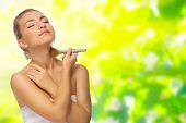 foto of face-powder  - Young girl applying face powder on spring floral background - JPG