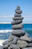 stock photo of desert christmas  - Christmas cairn - cairn built of black volcanic stones in a shape of Christmas tree on a beach of black and white pebbles on Fuerteventura Canary Islands Spain