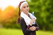 Portrait Of Happy Positively Looking Caucasian Fitness Woman With Drinking Water Outdoors. Light Eff