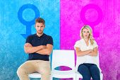 Young couple sitting in chairs not talking during argument against pink and blue