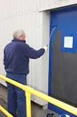 image of roller door  - A painter painting a door using a gloss roller - JPG
