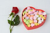 A box of Valentine's Day candy hearts and a single red rose on a white wood table. The rose is misted and the pastel candies are blank. Horizontal format.