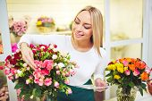 Female florist with touchpad counting roses in the shop