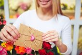 Female florist putting message for receiver in small envelope in rose bouquet