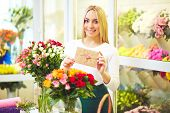 Happy florist with congratulation message in small envelope and fresh flowers near by looking at camera