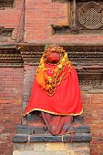 PATAN, NEPAL - APRIL 13 2014 : Statue Of Hamunan painted in red paste and cloaked in red fabric sitting outside Sundari Chowk in Patan, Nepal on 13 April 2014.