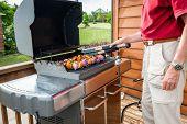Man set shish kebob skewers on a grill