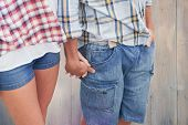 Couple in check shirts and denim holding hands against pale grey wooden planks