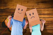 Couple wearing sad face boxes on their heads against wooden table with autumn leaves