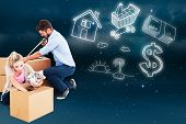 Young couple packing moving boxes against stars twinkling in night sky