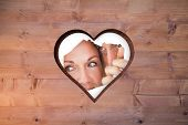 Couple looking through torn paper against heart in wood