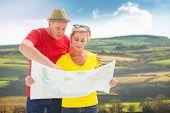 Lost tourist couple using map against scenic landscape