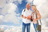 Happy tourist couple using the guidebook against blue sky with white clouds