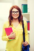 education concept - smiling redhead female student in eyeglasses with laptop bag and notebooks in library