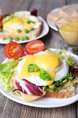stock photo of benediction  - Toast with egg Benedict and tomato on plate on wooden table - JPG