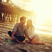 picture of couple sitting beach  - romantic couple sitting on beach with golden sunset by beach - JPG