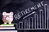 picture of piggy  - Pink piggy bank with glasses standing on books next to a blackboard with retirement savings message - JPG
