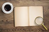 Diary or open book with loupe and coffee cup