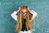 Crazy nerd blond student girl holding hair surprised expression in green chalk board