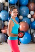 Blue eyes girl at gym weightlifting dumbbells in fitness training